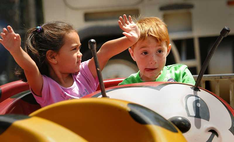 by: VERN UYETAKE - Erika Alsdorf and Tino Handris of West Linn take a spin on the Baby Bug rid at the West Linn Old Time Fair.