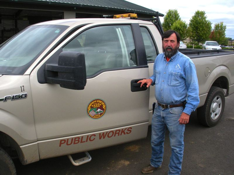 by: POST PHOTO: JIM HART - Martin Montgomery stands beside his office on wheels during one of his long and busy days as crew leader for the entire public works department.