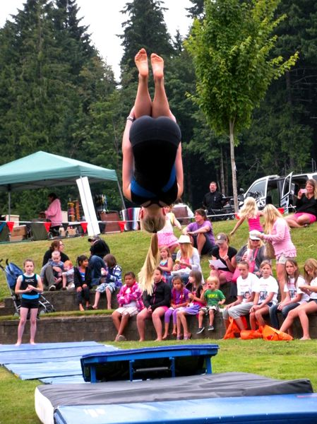 by: POST PHOTO: JIM HART - A member of the Northwest Gymnastics Training Center in Gresham demonstrates her skills for an audience of parents and children at the Family Fun Festival, held Saturday, July 20, at Sandy Bluff Park.