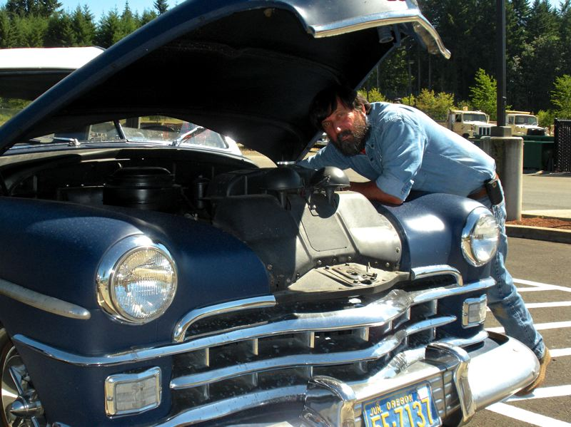by: POST PHOTO: JIM HART - During non-work hours, Martin Montgomery loves to restore classic cars. In this photo, he is pictured with the 1950 Chrysler he can be seen driving any day.