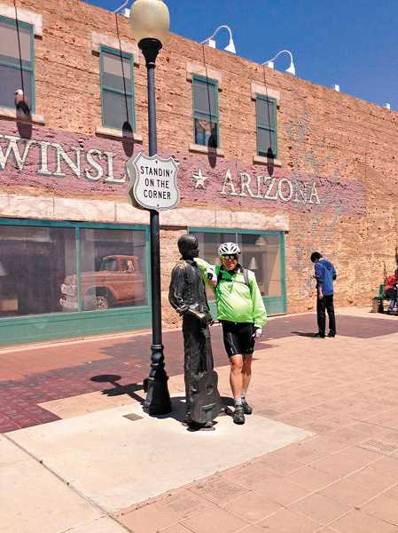 by: SUBMITTED - Bill MacKenzie revels in the opportunity to be photographed standin' on a corner in Winslow, Ariz.; such a fine sight to see. In the background mural you can see a girl (my lord!) in a flatbed Ford.
