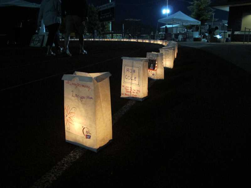 by: SUBMITTED PHOTO: ERIC SAMUELSON - A tradition of Relay for Life is to light luminarias in honor of those who have cancer, died of cancer or are survivors of cancer. The luminarias lined the track at Lake Oswego High School.