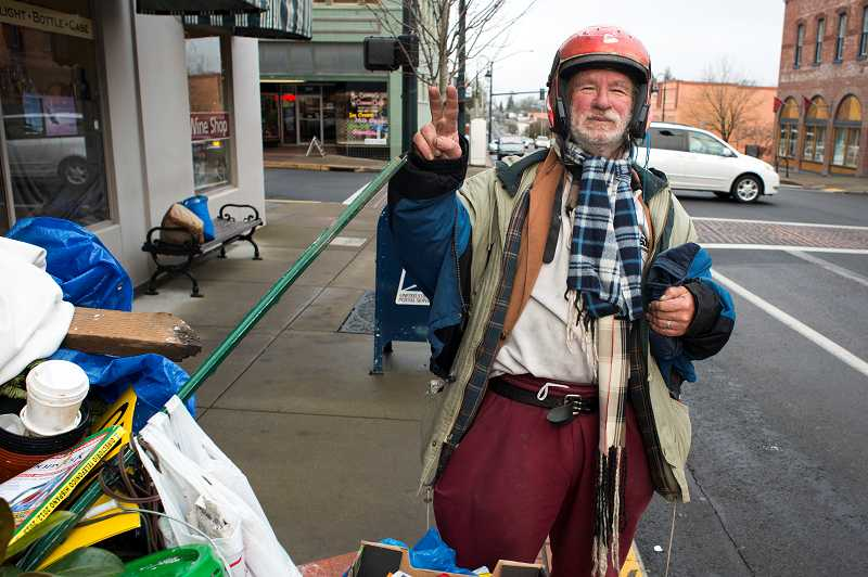 by: NEWS-TIMES PHOTO: CHASE ALLGOOD - Forest Grove icon John Wedell flashes a peace sign as he walks with his carts along Pacific Avenue. Wedell, 66, also spends time in the coastal community of Astoria, where his brother Steve lives.