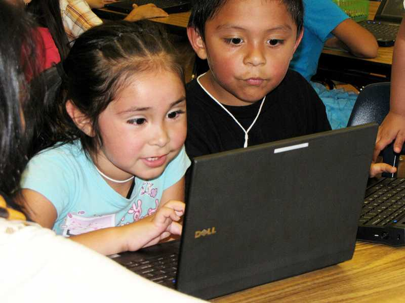 by: COURTESY PHOTO: CONNIE POTTER - Pre-schoolers Kimberly Velazquez (left) and Ariel Garcia-Gomez use an online library, which offers 4,000 titles in both English and Spanish.