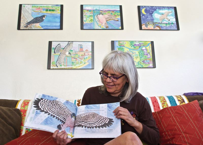 by: TRIBUNE PHOTOS: JAIME VALDEZ - North Portland artist Lisa Manning shows pages from her first book, Falcons in the City, a local environmental success story.