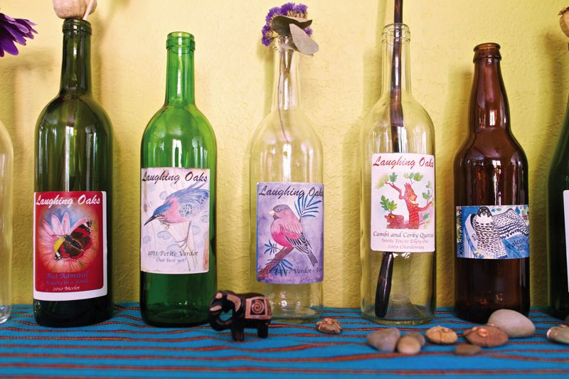 by: TRIBUNE PHOTOS: JAIME VALDEZ - Lisa Manning displays a row of wine bottle labels she designed in her art-filled home nearby the Willamette bluffs. Nature has always been her muse.
