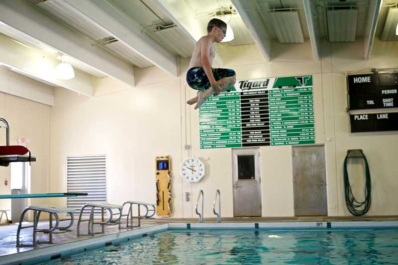 by: TIMES PHOTO: JAIME VALDEZ - Parker Stevenson, 11, jumps off the diving board during open swim at the Tigard swimming pool at Tigard High School. Three years after the Tigard-Tualatin Aquatic District was formed, the Board of Directors is looking at reducing the tax rate in the future from a maximum of 9 cents per $1,000 of assessed valuation.