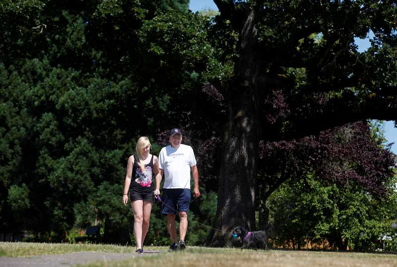 by: TIMES PHOTO: JONATHAN HOUSE - Brent Gant and his daughter Taylor take a walk through one of Oak Hills' neighborhood parks with Shasta. The neighborhood has been recognized as a historical development ahead of its time.