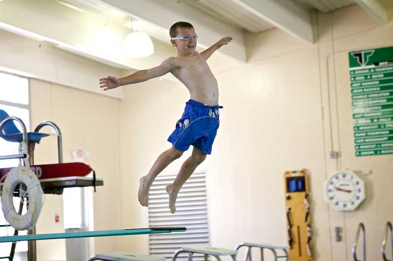 by: TIMES PHOTO: JAIME VALDEZ - Hogan Stevenson, 7, jumps off the diving board during open swim at the Tigard pool.