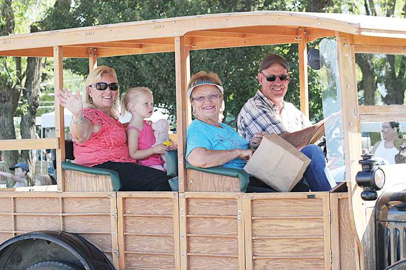 by: HOLLY M. GILL - Grand marshal for the fair, Sarah Miller, center, rides with Jim Carroll, her daughter, Kristy, and great-grandaughter, Tylie.