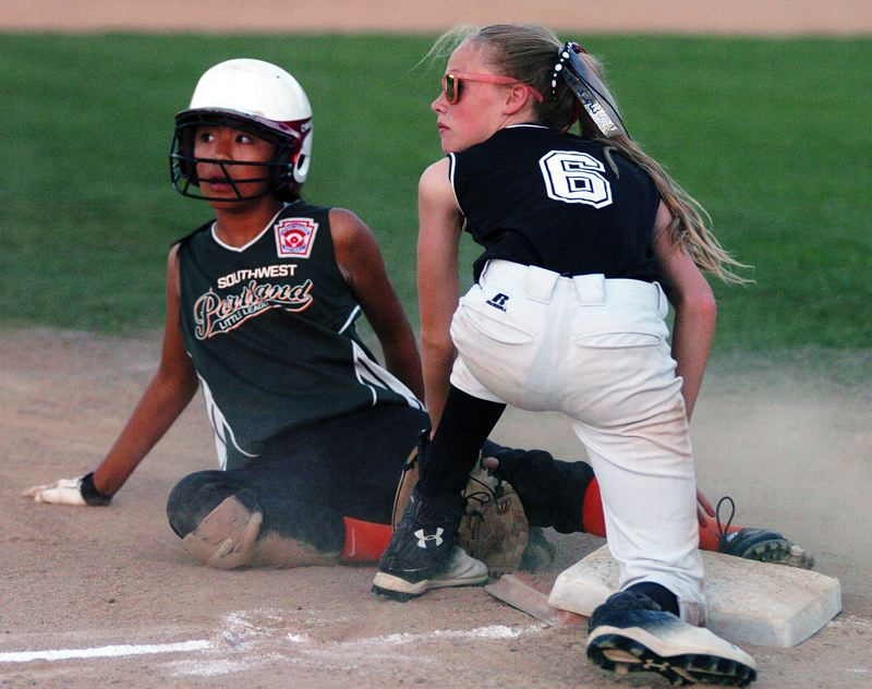 by: DAN BROOD - FOR THE DEFENSE -- Tualatin City shortstop Camille Hall (right) tags out Southwest Portland's Dechen Yehshopa at third base on a stolen-base attempt in Friday's game.