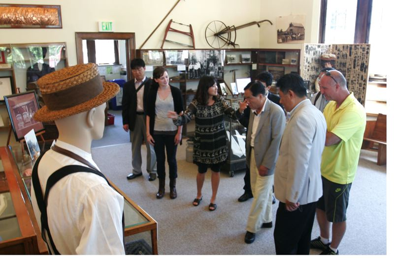 by: OUTLOOK PHOTO: JIM CLARK - Christy Weaver, a Gresham History Museum clerk, tours  Jae-sek Hahm, deputy mayor of Sokcho, and other South Korean delegates, through exhibits Wednesday, July 24.