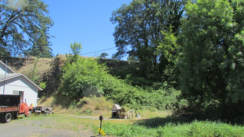 by: MARK MILLER - The basalt bluff in St. Helens that would be excavated under a development proposal that failed to obtain a required permit from the city, as seen from North 11th Street.