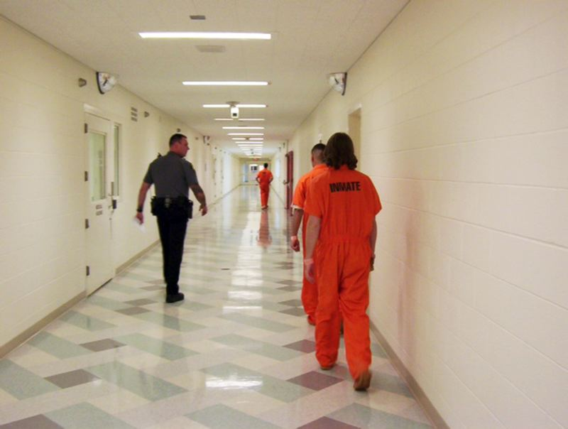 by: COURTESY OF WASHINGTON COUNTY SHERIFFS OFFICE - A Washington County Sheriffs deputy escorts inmates through a passageway in the jail.