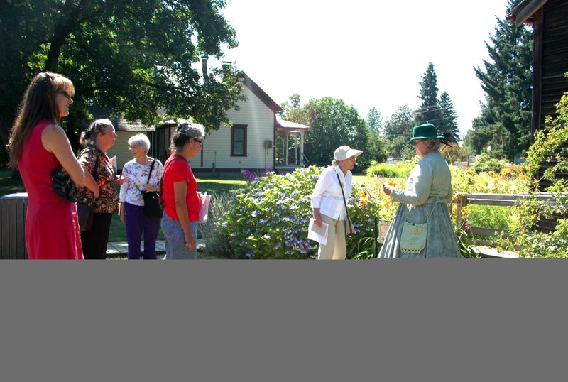 by: ISABEL GAUTSCHI - Gerri Morse, in pioneer dress, tells of Philip Foster Farms historic roses.