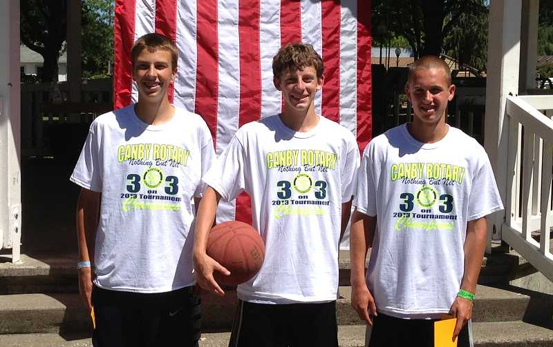 by: SUBMITTED PHOTO - Wilsonville High athletes Chris Riewald (left), Kaden Ogles and Sam Bullock won their second-straight title at the Nothing But Net charity basketball tournament July 27 in downtown Canby. The 3-on-3 Kings went 5-0.