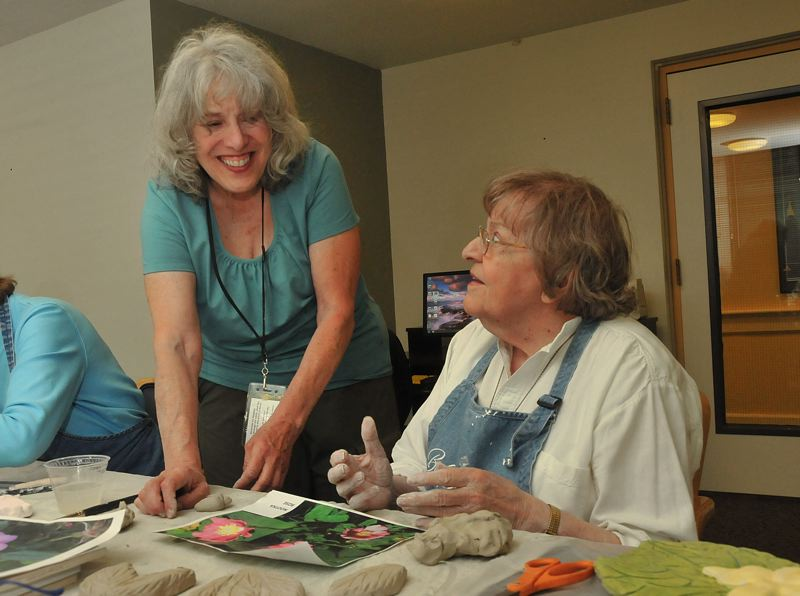 by: CONNECTION PHOTO: VERN UYETAKE - At a recent workshop at Terwilliger Plaza, artist Lynn Takata helps Joan Rague work on a contribution to the Marquam Mosaic.