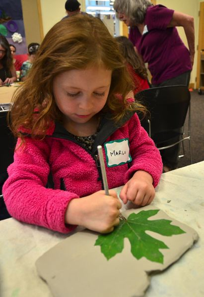 by: CONNECTION PHOTO: VERN UYETAKE - Marlo Dabareiner traces a leaf on a slab a clay at a Marquam Mosaic workshop at the Hillsdale Library.