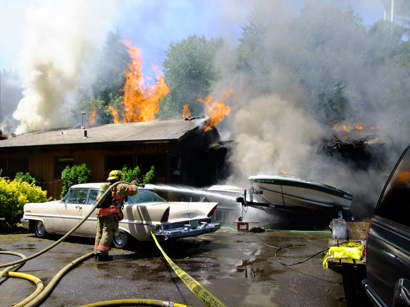 by: SUBMITTED PHOTO: BRIAN HUGHES - Portland Fire & Rescue firefighters extinguish a house fire on Southwest Dolph Court.