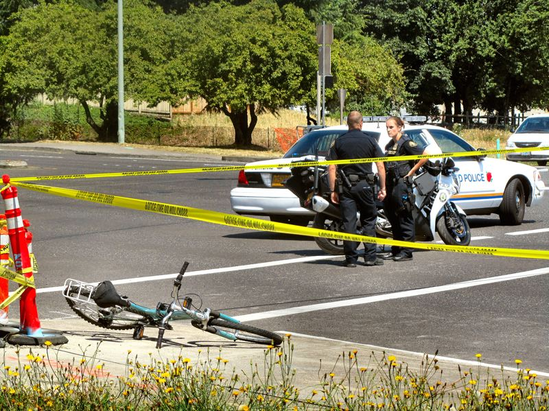 by: ERIC NORBERG - The damaged bike lay on the sidewalk while officers closed McLoughlin to make their investigation.