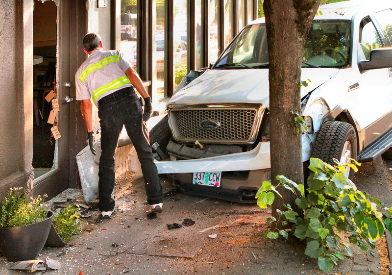 by: DAVID F. ASHTON - A tow driver examines the broken light pole that apparently shielded the coffee shops front from further damage.