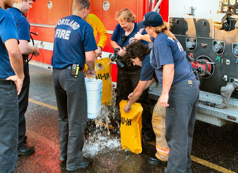 by: DAVID F. ASHTON - The crew of Westmorelands Fire Engine 20 fills water backpacks, before heading off to make sure all hotspots from the brushfire have been doused.