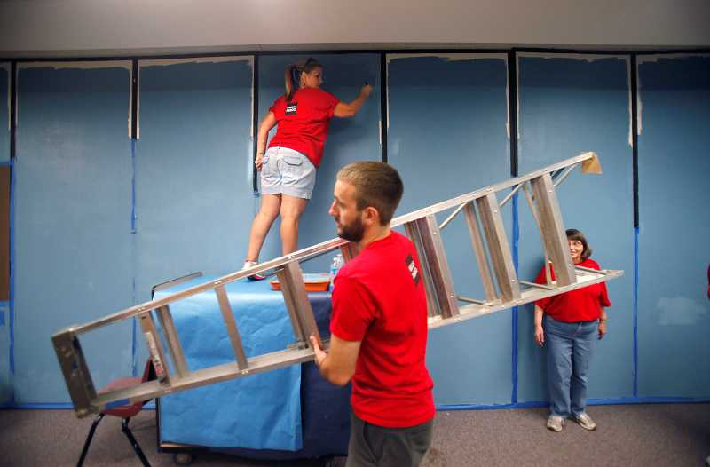 by: TIMES PHOTO: JONATHAN HOUSE - Dyan Loza paints a classroom wall while Michael Clouse moves a ladder during the Wells Fargo Barnhart Center's annual Volunteer Day, where employees donated their time Saturday to help Five Oaks Middle School and the Rachel Carson School of Environmental Science.