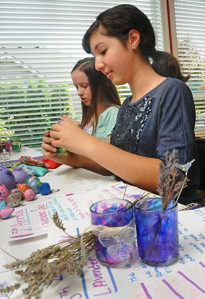 by: TIDINGS PHOTO: VERN UYETAKE - Lavender Girls Sydney Steinberg, right, and Emily Henning put finishing touches on tea lights that will be part of the sale.