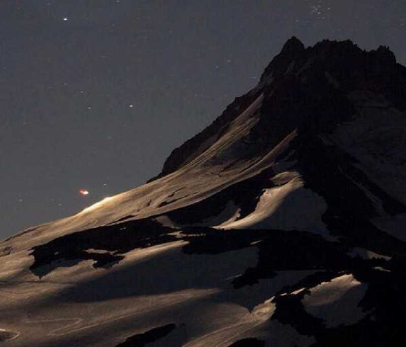 by: DESCHUTES COUNTY S&R FACEBOOK PAGE - Blackhawk helicopter search lights illuminate a spot on the left of the photo as it searches for the climbing accident victim on Mount Jefferson.