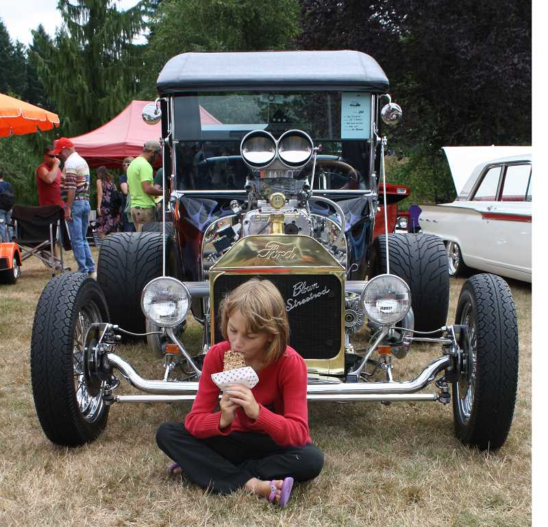 by: POST PHOTO: NEIL ZAWICKI - It wasnt all Kiwanis bars and T-Buckets at the Kiwanis Fly-in Crusie in. It also was Corvairs and kit planes. Gwen Hawkins, 8, enjoys her $3 Kiwanis bar inbetween browsing the classic cars.