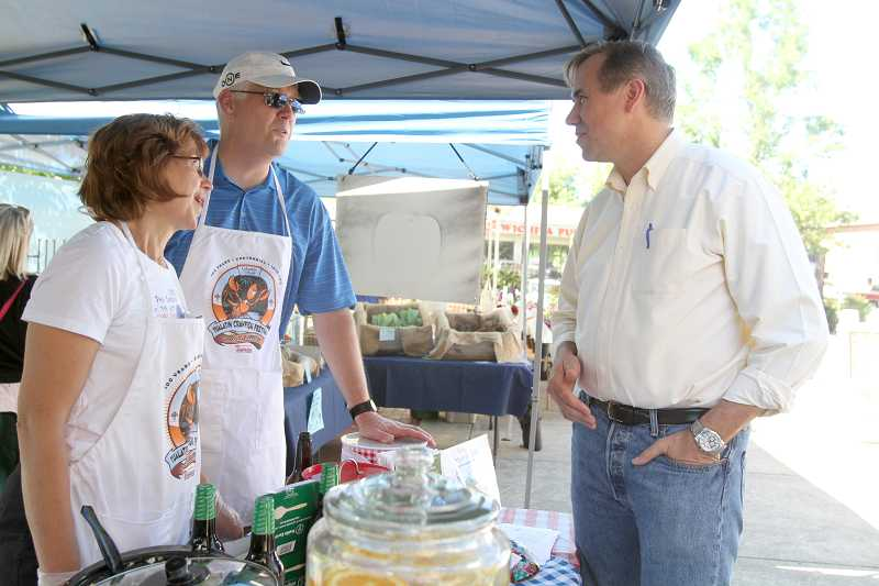by: TIMES PHOTO: JONATHAN HOUSE - U.S. Sen. Jeff Merkley chats with Tualatin Chamber representatives Brian and Carolyn Horn during a visit to the Tualatin Farmers Market on Friday.