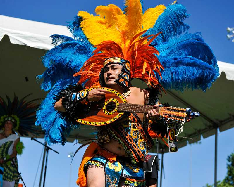 by: SUBMITTED PHOTO: JOHN LARIVIERE - Huitzilopochtli dance troupe captain José Carlos performs a traditional Aztec dance honoring the sun while wearing a colorful head dress as part of the Beaverton International Celebration.