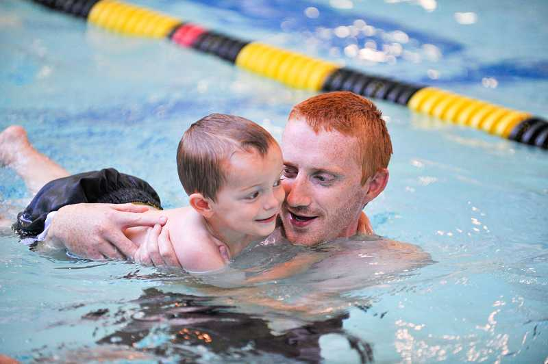 by: SUBMITTED PHOTO: JOHN LARIVIERE - Tyler Nelson helps his son Reece, 2, during the swim portion of the Family Triathlon at Saturday's Party in the Park.