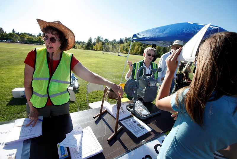 by: TIMES PHOTO: JONATHAN HOUSE - Mary Bauman, left, and Julie Stack of CERT show patrons of the Tigard Emergency Preparedness Field Day how to properly turn off their utilities in case of an emergency.