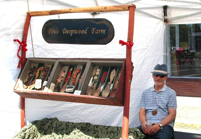 by: ISABEL GAUTSCHI - Phil Lingelbach, artist and chairman of the Estacada Development Association, enjoyed a prime vending space near the main stage. He showed off his hand crafted wooden spoons.