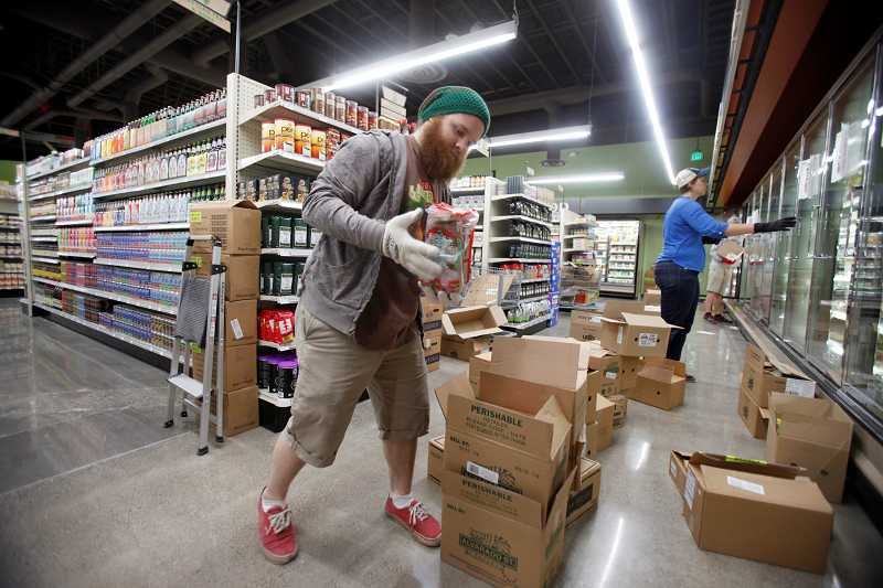 by: TIMES PHOTO: JONATHAN HOUSE - Daniel Ricchi unpacks boxes of gluten-free breads in the new location of Natural Grocers in Beaverton. The store will have its grand opening on Aug. 6.