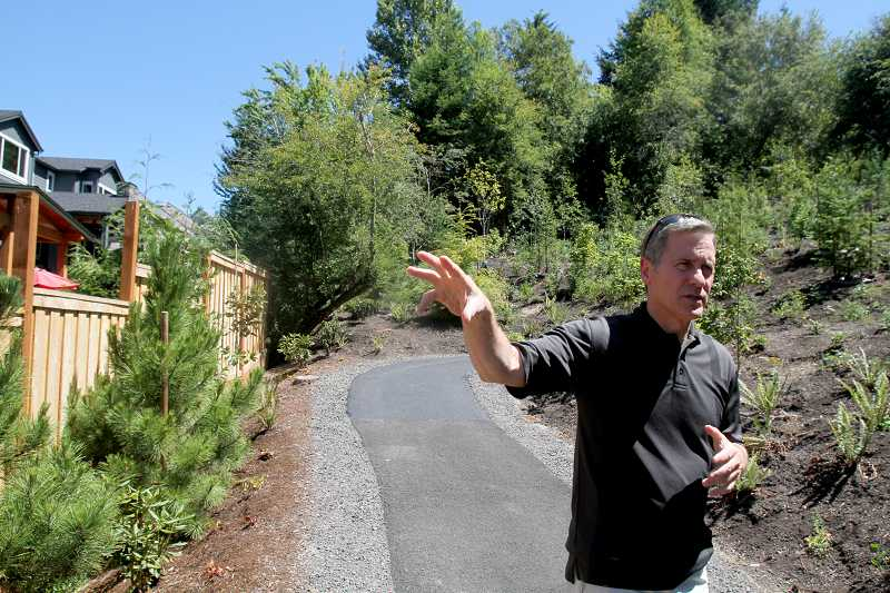 by: TIMES PHOTO: JONATHAN HOUSE - Cedar Mill resident Bill Booth talks about his frustration with the Tualatin Hills Park and Recreation District, over its new Bluffs Park development. Booth feels officials didnt pay enough attention to neighborhood oppostion of leveling trees and paving a concrete trail.