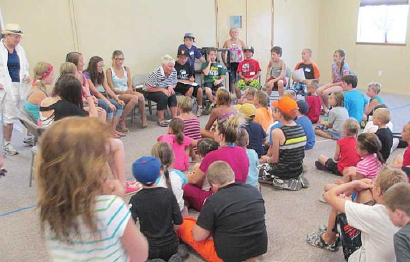 by: JOHN BOWLER - Senior Sylvia Kimbley, back center, tells children a story during Crooked River Ranch's Summer Recreation Program. Started in the 1990s, the program is run primarily by Ranch Seniors, and draws over 50 Ranch children.
