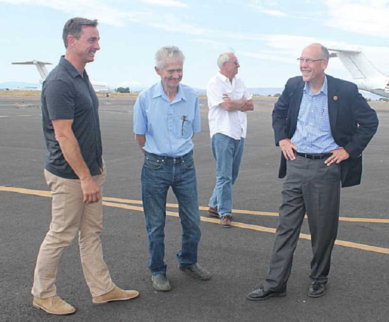 by: HOLLY M. GILL - From left, Kevin McCullough and Jack Erickson, owners of Erickson Aero Air, and lobbyist Alan Ross (back) visit with U.S. Rep. Greg Walden at the Erickson Aero Tanker facility July 26, at the Madras Municipal Airport.