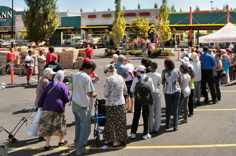 by: DAVID F. ASHTON - Recipients patiently wait in line at Eastport Plaza on July 10th, ready to receive packages of food, household goods, and clothing.