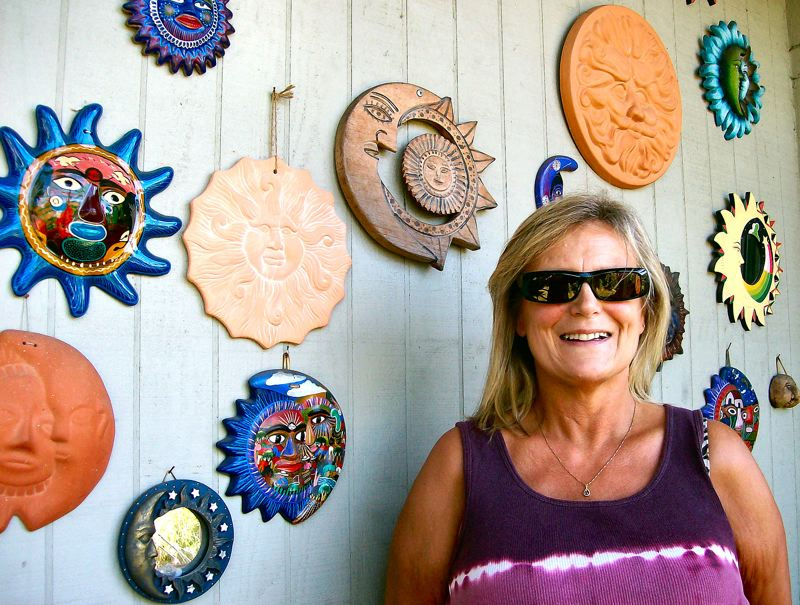 by: RITA A. LEONARD - Laurie Webster is shown with some of the suns, moons, and stars decorating her Inner Southeast front porch. As you might imagine, someone who works with so many suns must wear shades.