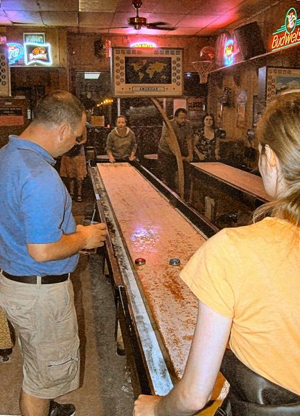 by: DANA BECK - Table shuffleboard games surged in popularity during WW II, as soldiers and sailors played the games at overseas taverns and USO Clubs. In the 1950s the servicemen brought the game back to the States, and many tournaments were held. This is one of the three shuffleboards that remained in the Black Cat Tavern as it prepared to close for good.