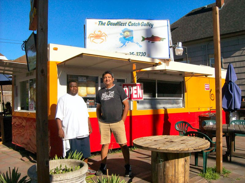 by: RITA A. LEONARD - Owner Raffael Gaxiola, at right, and chef Howard Jerry have opened The Deadliest Catch Galley - a new food cart restaurant on S.E. Milwaukie Avenue in Brooklyn.