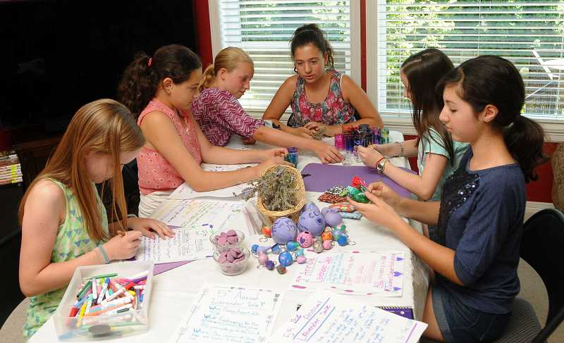 by: TIDINGS PHOTO: VERN UYETAKE - From left, Lauren Henning, Audrey Minch, Lauren Jones, Abigail Minch, Emily Henning and Sydney Steinberg work on their lavender crafts.