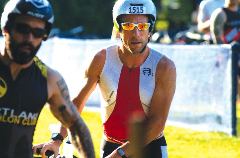 by: PAMPLIN MEDIA GROUP: DAVID BALL - Hillsboros Joe English gets through the bike transition area during his win at the Blue Lake sprint triathlon Sunday.