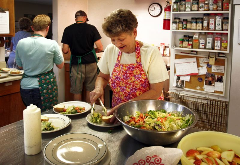 by: OUTLOOK PHOTO: JIM CLARK - Zarephath volunteer Sonja Flener scoops salad on plates served to the hungry.
