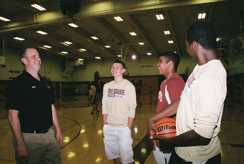 by: PHOTO BY: JOHN DENNY - Milwaukie head basketball coach Scott Bays visits with sophomores-to-be (from left) Vasiliy Voznyuk, Isaiah Gentry and Isaac Mbuyamba during a summer youth basketball camp at the high school.