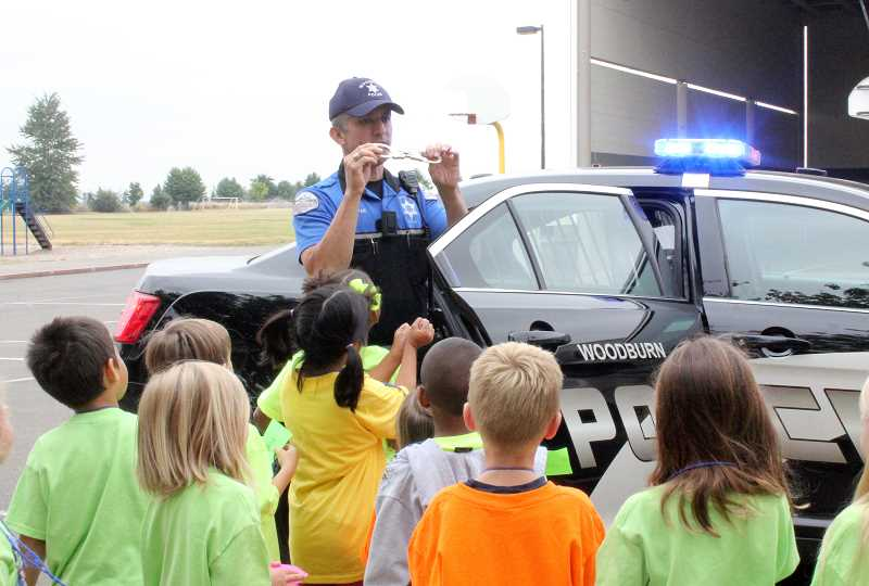 by: LINDSAY KEEFER - Woodburn Police officer Jorge Gaspar showed children his handcuffs and police cruiser at the annual Safety Camp last week.