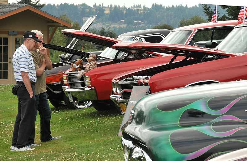 by: VERN UYETAKE - Mark Brown of West Linn, left, and his friend Mark Kaiser, who was visiting from Baltimore, look over the cars on display at the West Linn Adult Community Center on Friday.