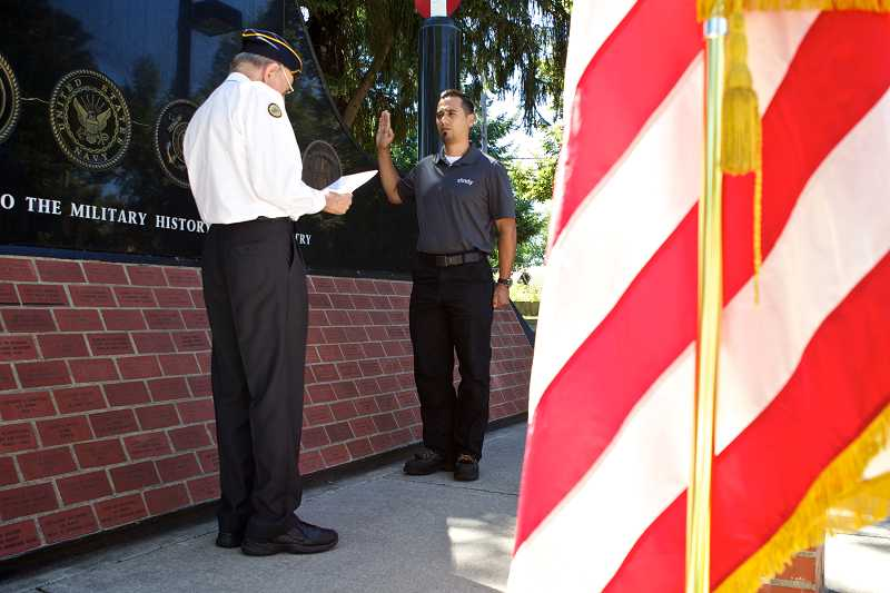by: TIMES PHOTO: JAIME VALDEZ - Louis Haga, a member of the Beaverton-based American Legion Post No. 124, initiates Abraham Trejo, a former U.S. Ranger Marine soldier, into the Air Force at a ceremony at Veterans Memorial Park on Tuesday afternoon.
